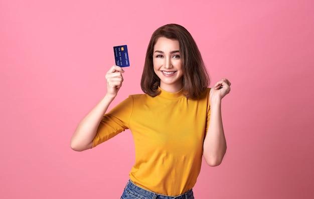 Młoda kobieta trzyma kartę kredytową w dorywczo żółtej sakiewce ze wspaniałym zaufaniem i pewnością do transakcji pieniężnej na białym tle na jasnoróżowej ścianie.
