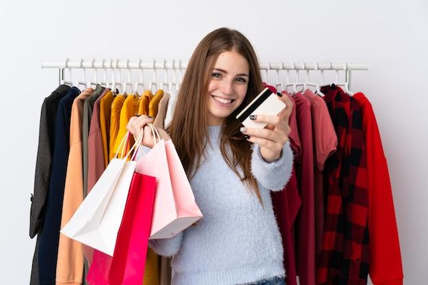 Młoda kobieta trzyma kartę kredytową w sklepie odzieżowym