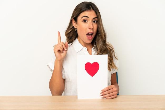 Młoda kobieta trzyma kartę walentynki wyrażające emocje na białym tle