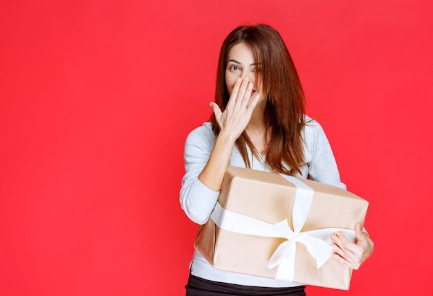 Młoda kobieta trzyma kartonowe pudełko i wygląda na zaskoczoną i pozytywnie nastawioną
