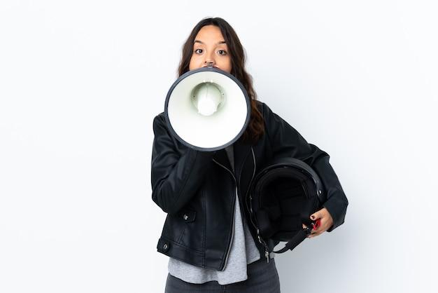 Młoda kobieta trzyma kask motocyklowy na białym tle krzycząc przez megafon