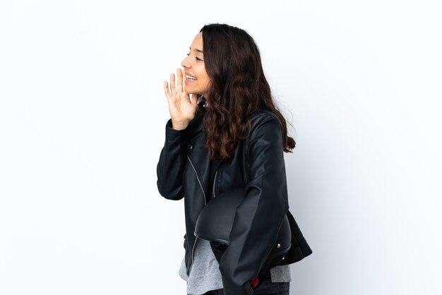 Młoda kobieta trzyma kask motocyklowy na białym tle krzycząc z szeroko otwartymi ustami do bocznych