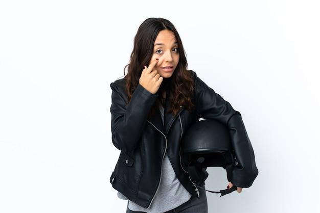 Młoda kobieta trzyma kask motocyklowy na białym tle, pokazując coś