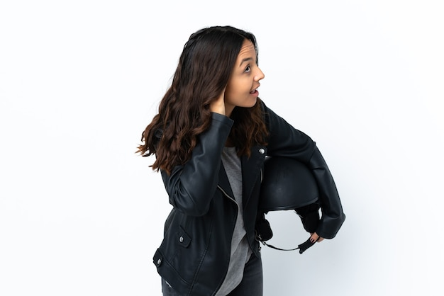 Młoda kobieta trzyma kask motocyklowy na białym tle, słuchając czegoś, kładąc rękę na uchu
