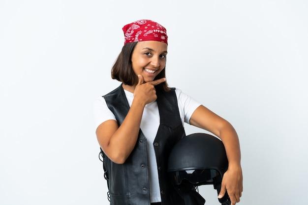 Młoda kobieta trzyma kask motocyklowy na białym tle