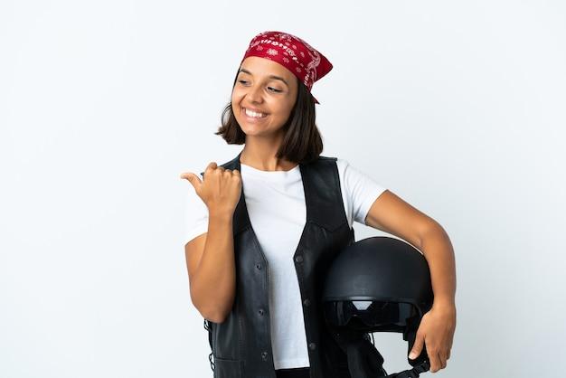 Młoda kobieta trzyma kask motocyklowy na białym, wskazując na bok, aby przedstawić produkt