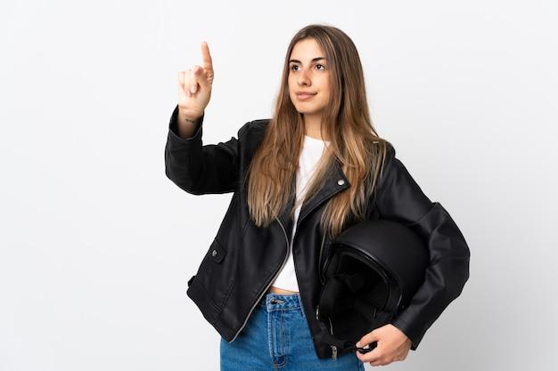 Młoda kobieta trzyma kask motocyklowy na na białym tle biały dotykając na przezroczystym ekranie