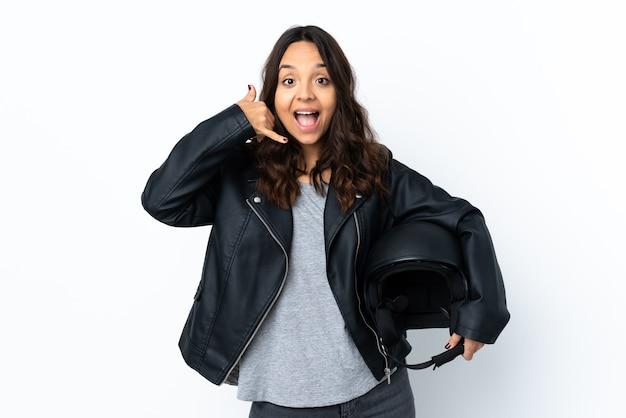 Młoda kobieta trzyma kask motocyklowy na na białym tle co telefon gest. oddzwoń do mnie znak