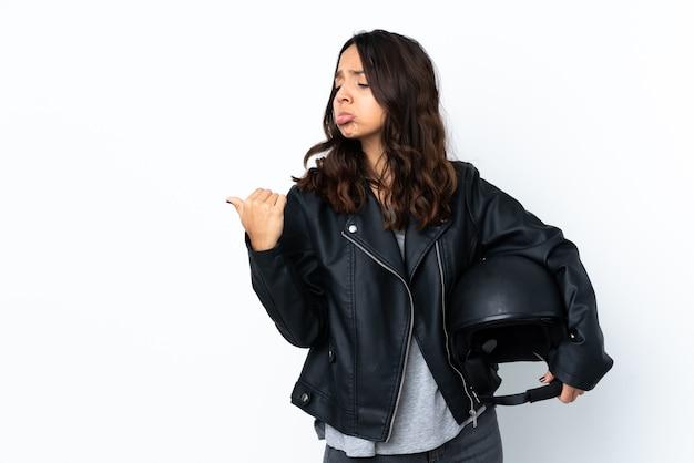 Młoda kobieta trzyma kask motocyklowy na na białym tle nieszczęśliwy i wskazując na bok