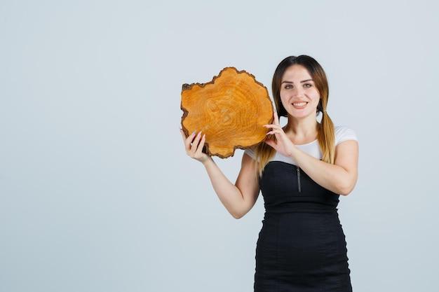 Młoda kobieta trzyma kawałek pnia drzewa na ramieniu