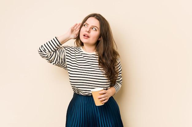 Młoda kobieta trzyma kawę próbuje słuchać plotki.