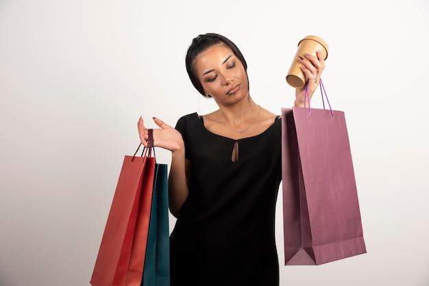 Młoda kobieta trzyma kilka toreb na zakupy i filiżankę kawy.