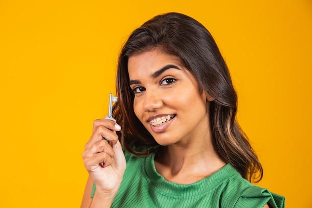 Młoda kobieta trzyma klucz do nowego domu.