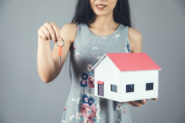 Młoda kobieta trzyma klucz i model domu