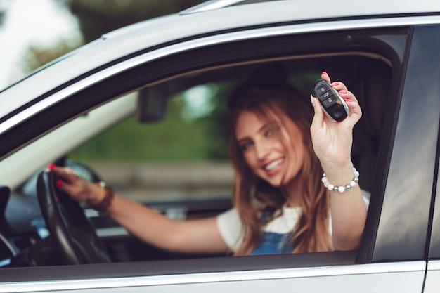Młoda kobieta trzyma klucze do nowego samochodu