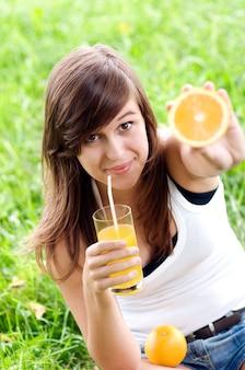 Młoda kobieta trzyma koktajl pomarańczowy i witaminowy