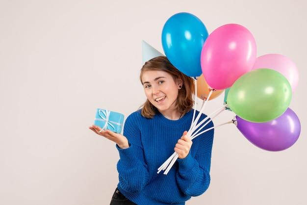 Młoda kobieta trzyma kolorowe balony i mały prezent na białym tle