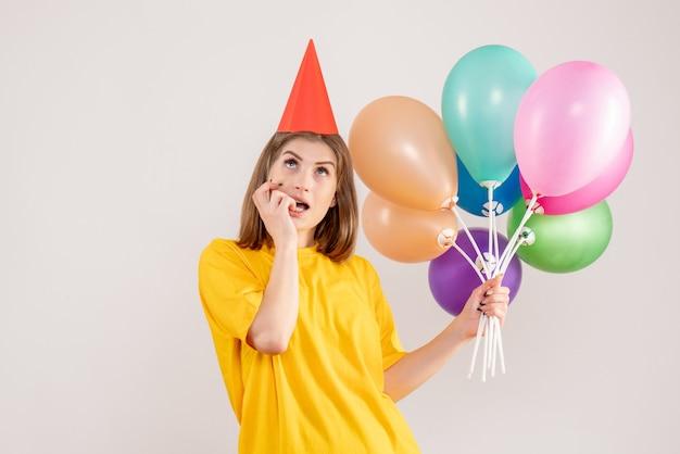 Młoda kobieta trzyma kolorowe balony i marzy na białym tle