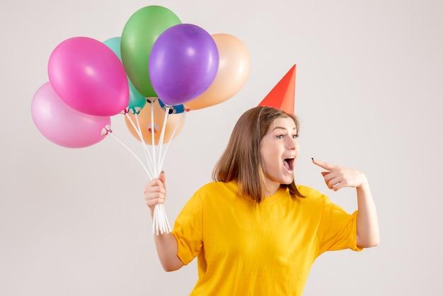 Młoda kobieta trzyma kolorowe balony na białym tle