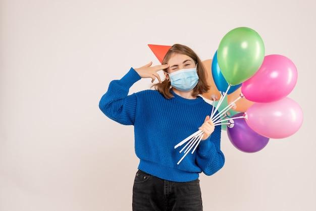 Młoda kobieta trzyma kolorowe balony w masce na białym tle