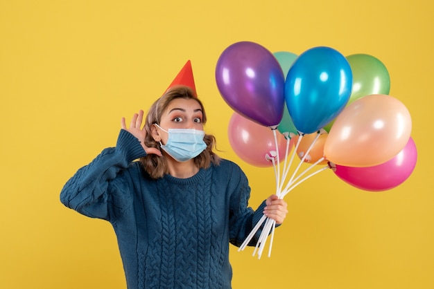 Młoda kobieta trzyma kolorowe balony w masce na żółto