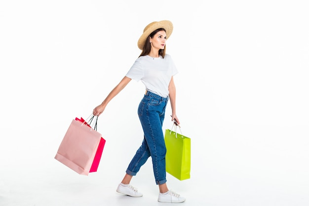 Młoda kobieta trzyma kolorowe torby odizolowywać na biel ścianie