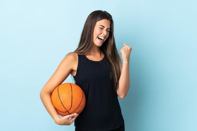 Młoda kobieta trzyma koszykówkę patrząc szczęśliwy