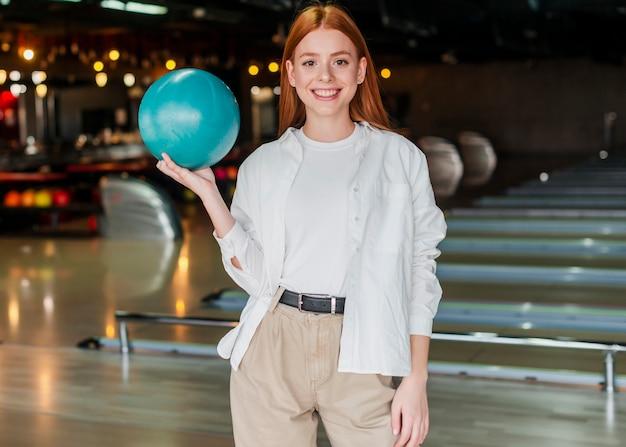Młoda kobieta trzyma kręgle piłkę