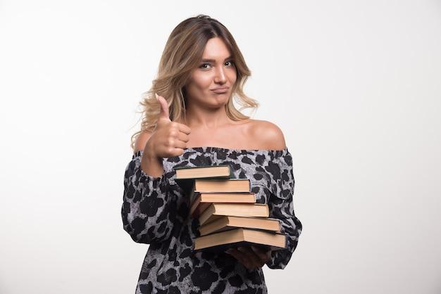 Młoda kobieta trzyma książki pokazując kciuki do góry.