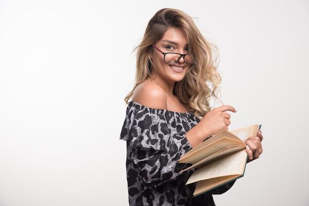 Młoda kobieta trzyma książki wskazując palcami.