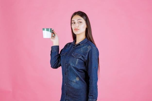 Młoda kobieta trzyma kubek białej zielonej kawy i pachnie