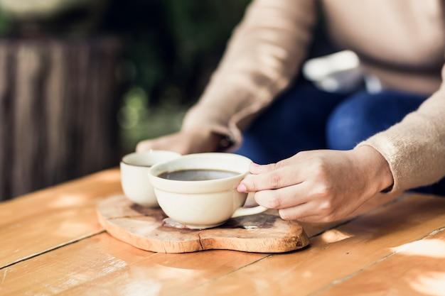 Młoda kobieta trzyma kubek gorącej kawy w widoku przyrody