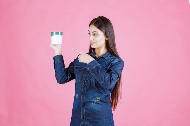 Młoda kobieta trzyma kubek kawy i wskazuje na to