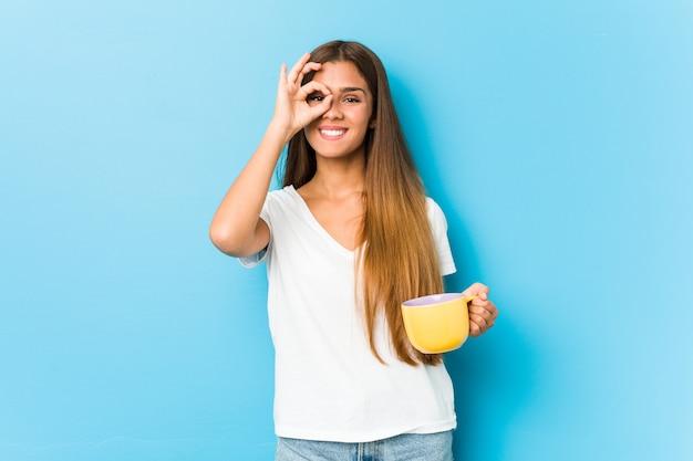 Młoda kobieta trzyma kubek kawy podekscytowany, trzymając ok gest na oko