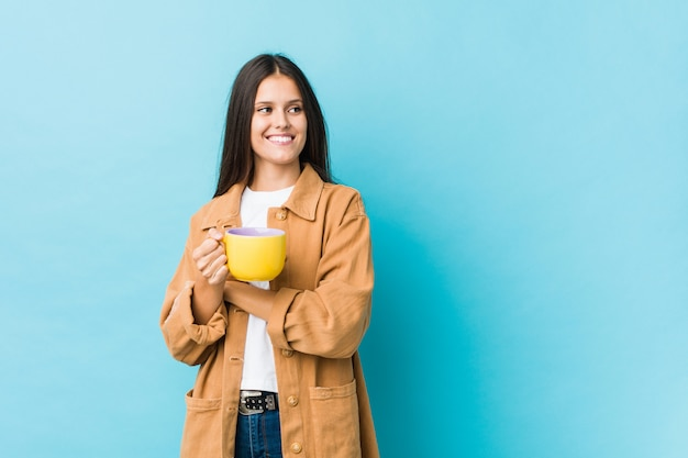 Młoda kobieta trzyma kubek kawy uśmiecha się pewnie ze skrzyżowanymi rękami