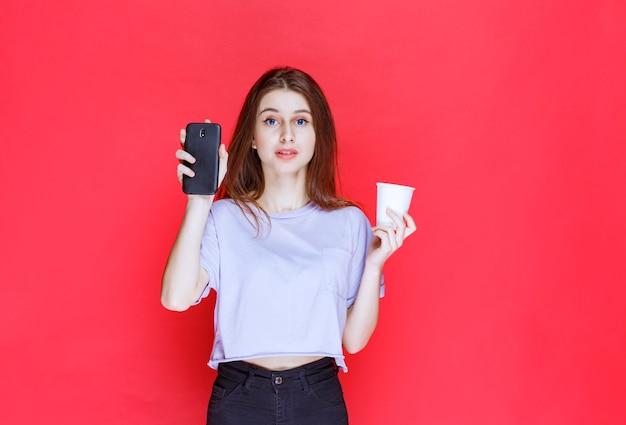 Młoda kobieta trzyma kubek napoju i czarny smartfon z rozczarowaną twarzą.