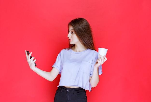 Młoda kobieta trzyma kubek napoju i sprawdza jej wiadomości.
