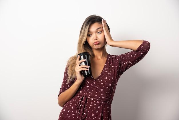 Młoda kobieta trzyma kubek napoju na białej ścianie.