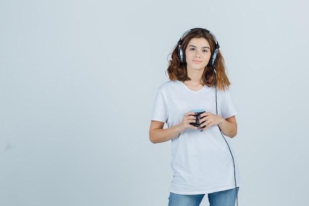 Młoda kobieta trzyma kubek napoju w białej koszulce i wygląda wesoło. przedni widok.