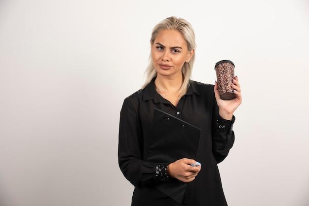 Młoda kobieta trzyma kubek ze schowka na białym tle. wysokiej jakości zdjęcie