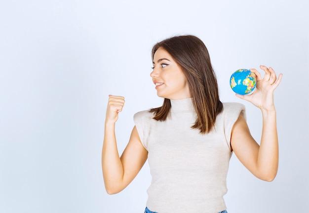 Młoda kobieta trzyma kulę kuli ziemskiej i wskazuje kciukiem.