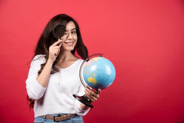 Młoda kobieta trzyma kulę ziemską i patrząc na nią z lupą. zdjęcie wysokiej jakości