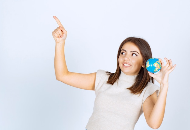 Młoda kobieta trzyma kulę ziemską i wskazuje palcem wskazującym w górę