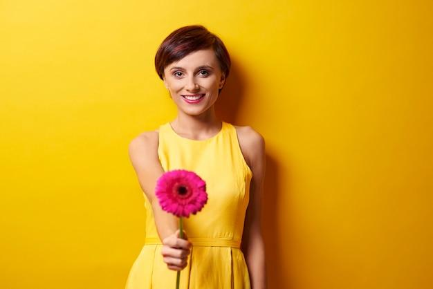 Młoda kobieta trzyma kwiat stokrotki gerbery