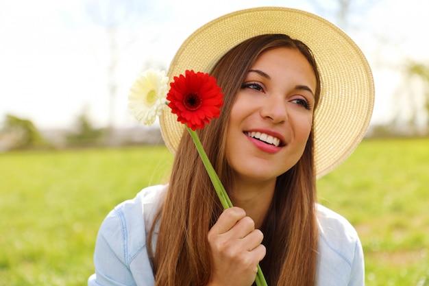 Młoda kobieta trzyma kwiaty gerbera