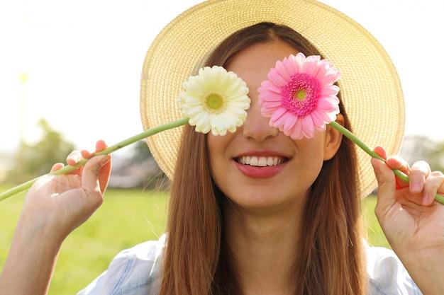 Młoda kobieta trzyma kwiaty na oczach