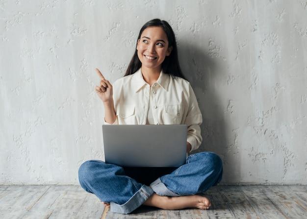 Młoda kobieta trzyma laptopa i patrząc w górę