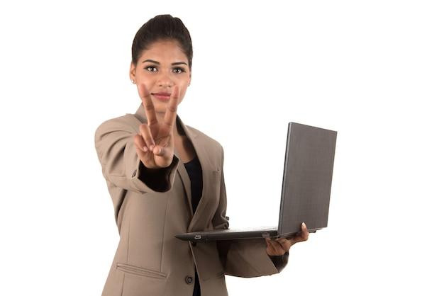Młoda kobieta trzyma laptopa, pokazując znak zwycięstwa. na białym tle