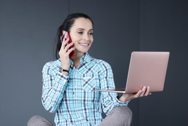 Młoda kobieta trzyma laptopa w dłoniach i rozmawia przez telefon. koncepcja pracy niezależnej