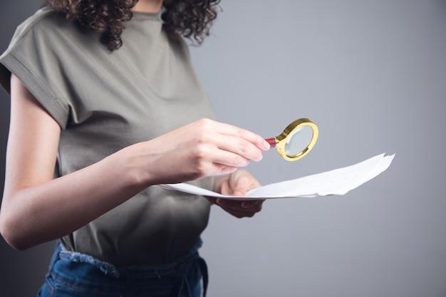 Młoda kobieta trzyma lupę i dokument